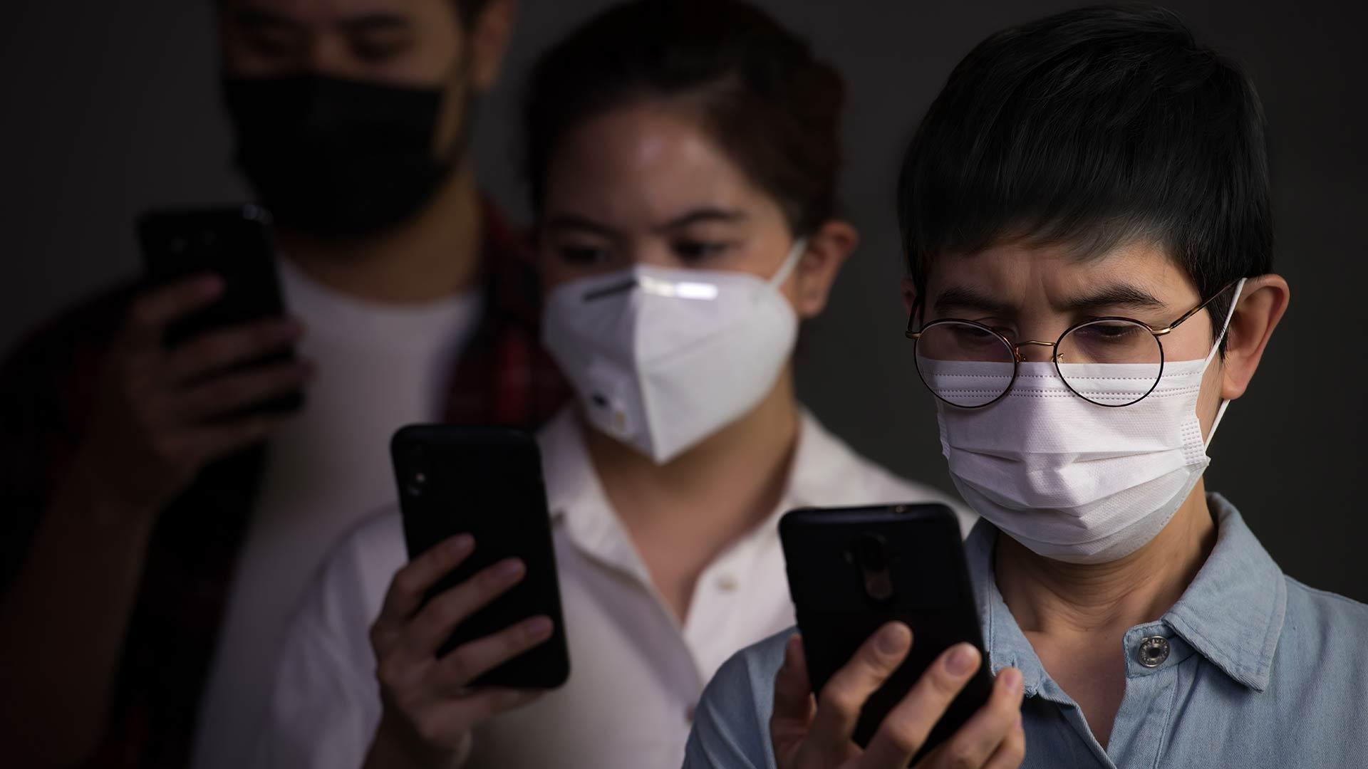 Люди в масках с телефонами